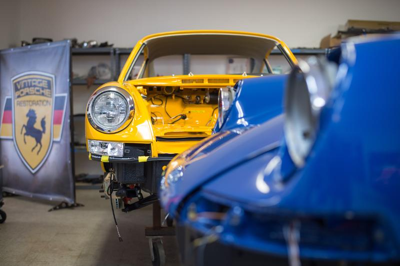 two porsches in assembly room in various stages of the assembly process