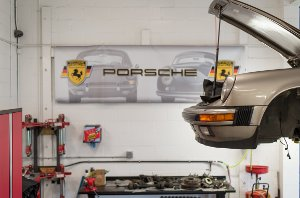 Porsche in shop on a lift with a link to the about restorations page